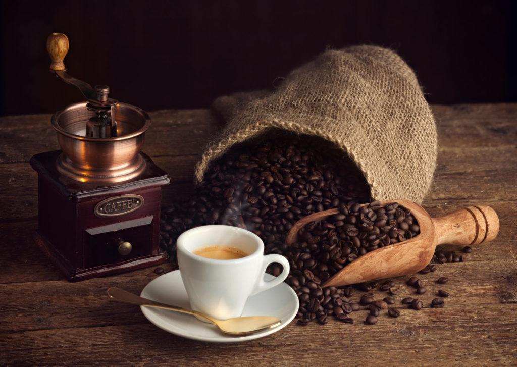 Kaffeemühle mit Espressotasse Kaffeesack mit Kaffeebohnen auf Holzbrett
