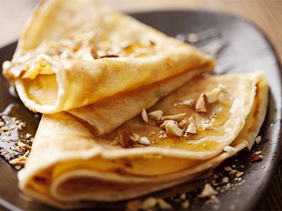 Crepes gefaltet und bestrichen mit Ahornsirup auf braunen Teller mit Nussstückchen im Da Roberto Café in Hachenburg im Habakuk