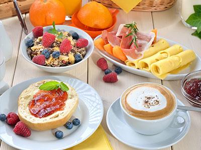 Frühstückstisch mit Cappuccino in Kaffeetasse, Brötchen mit Marmelade, Müsli mit Obst und Käse-Früchteteller im Da Roberto Café in Hachenburg im Habakuk
